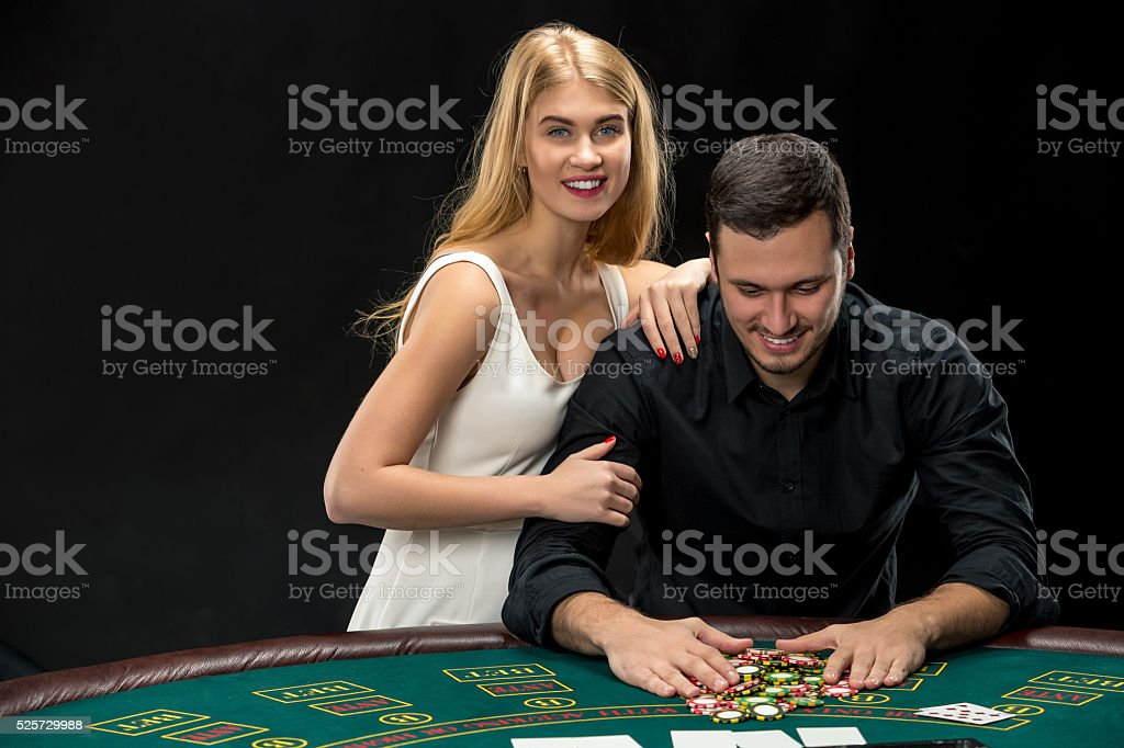 Young couple playing poker. Man taking poker chips after winning stock photo