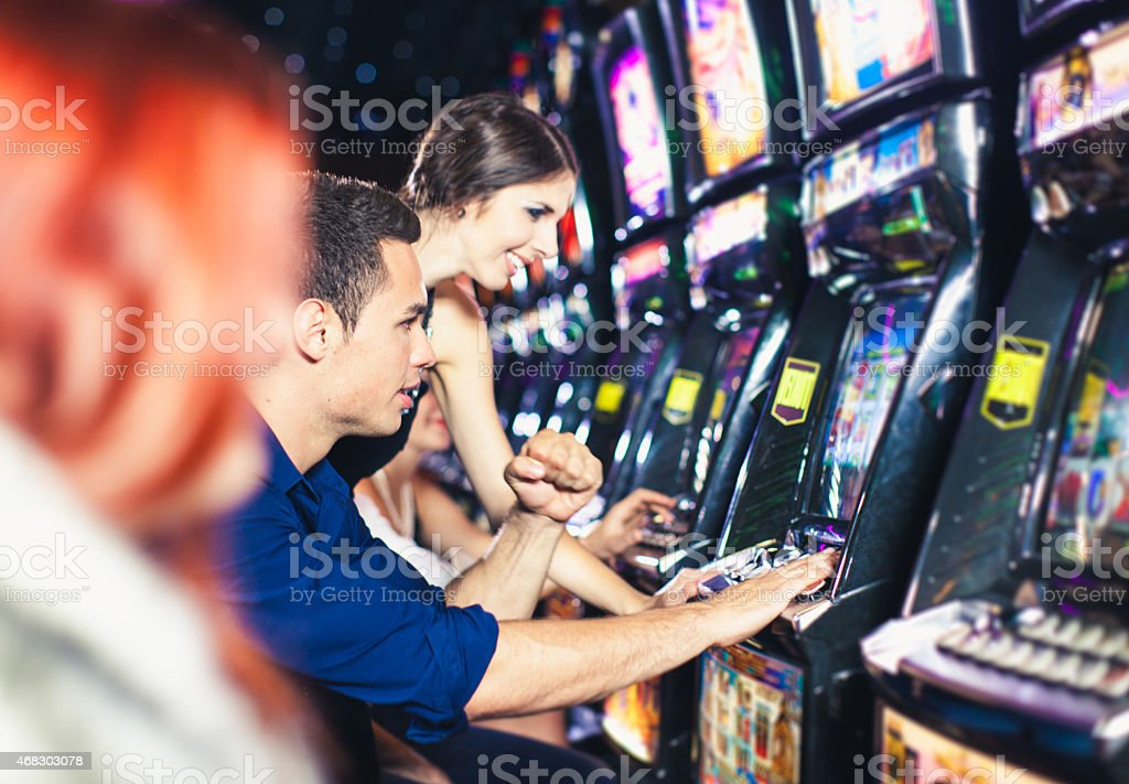 Young couple playing slot machines at the Casino stock photo