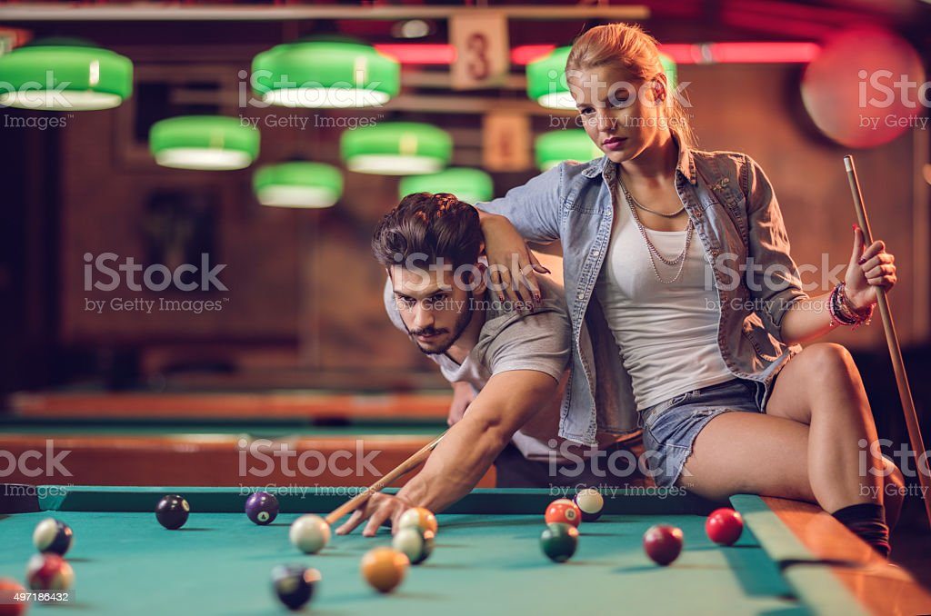 Young couple playing snooker in a pool hall. stock photo