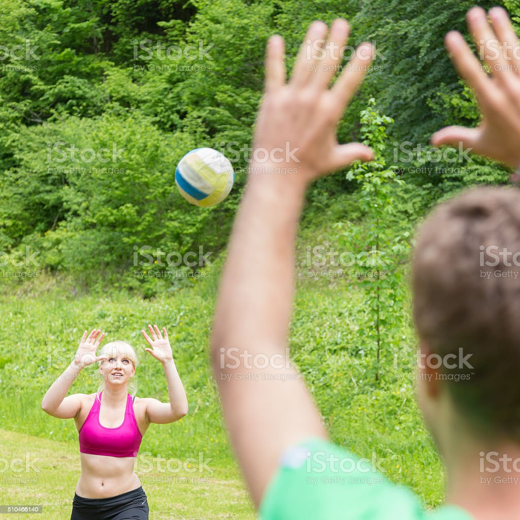 Young couple playing volleyball in park. stock photo