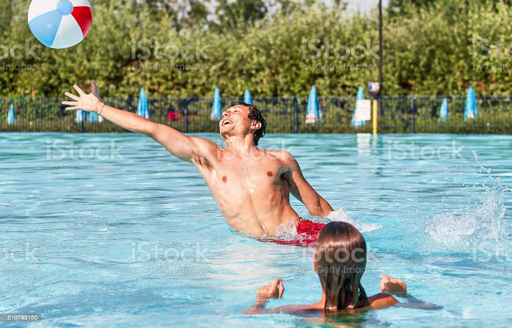Young couple playing with beach ball on swimming pool stock photo