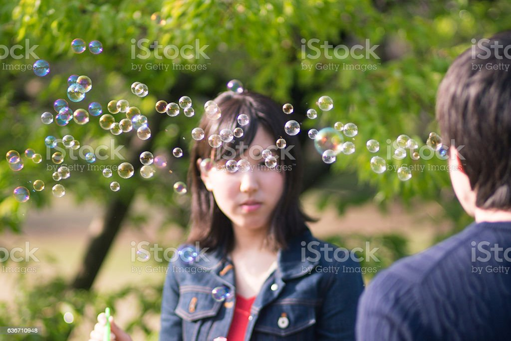 Young couple playing with soap bubbles in park stock photo