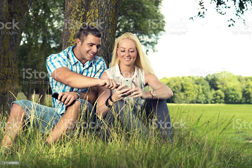 Young couple plays with smart phone outside royalty-free stock photo