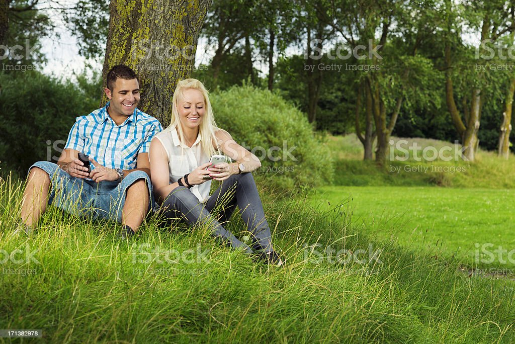 Young couple plays with smart phones outside royalty-free stock photo