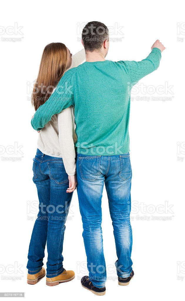 young couple pointing at wal Back view stock photo