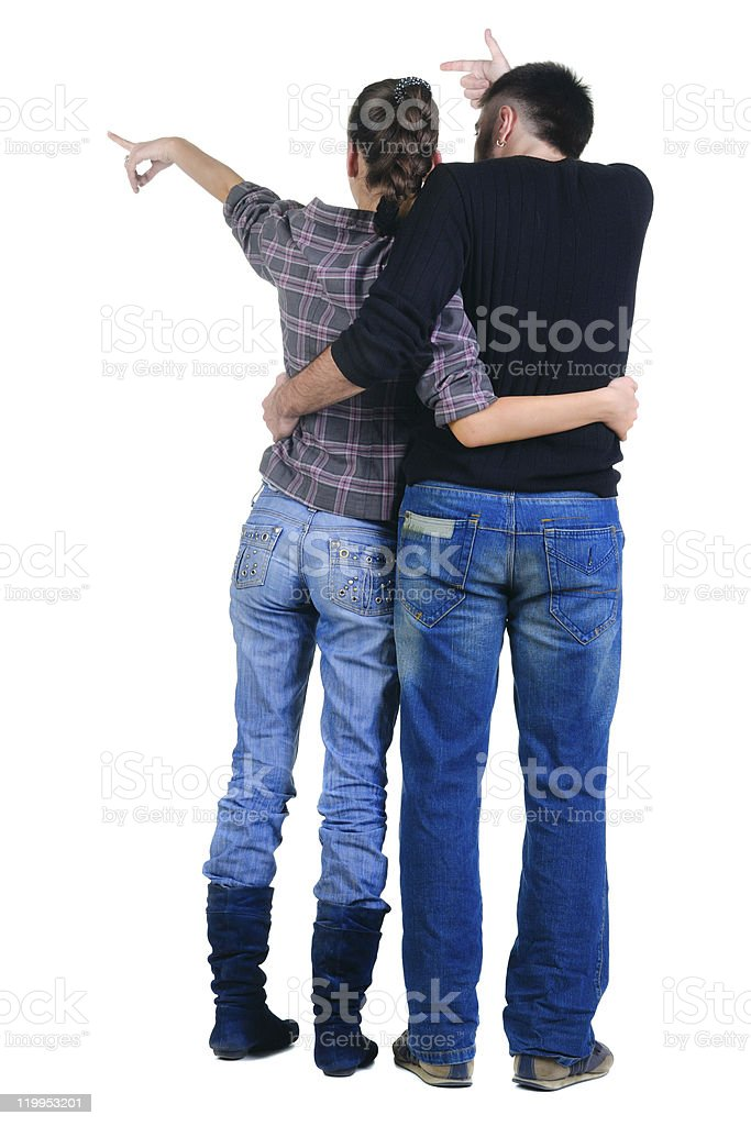 Young couple pointing at wall. Rear view. royalty-free stock photo
