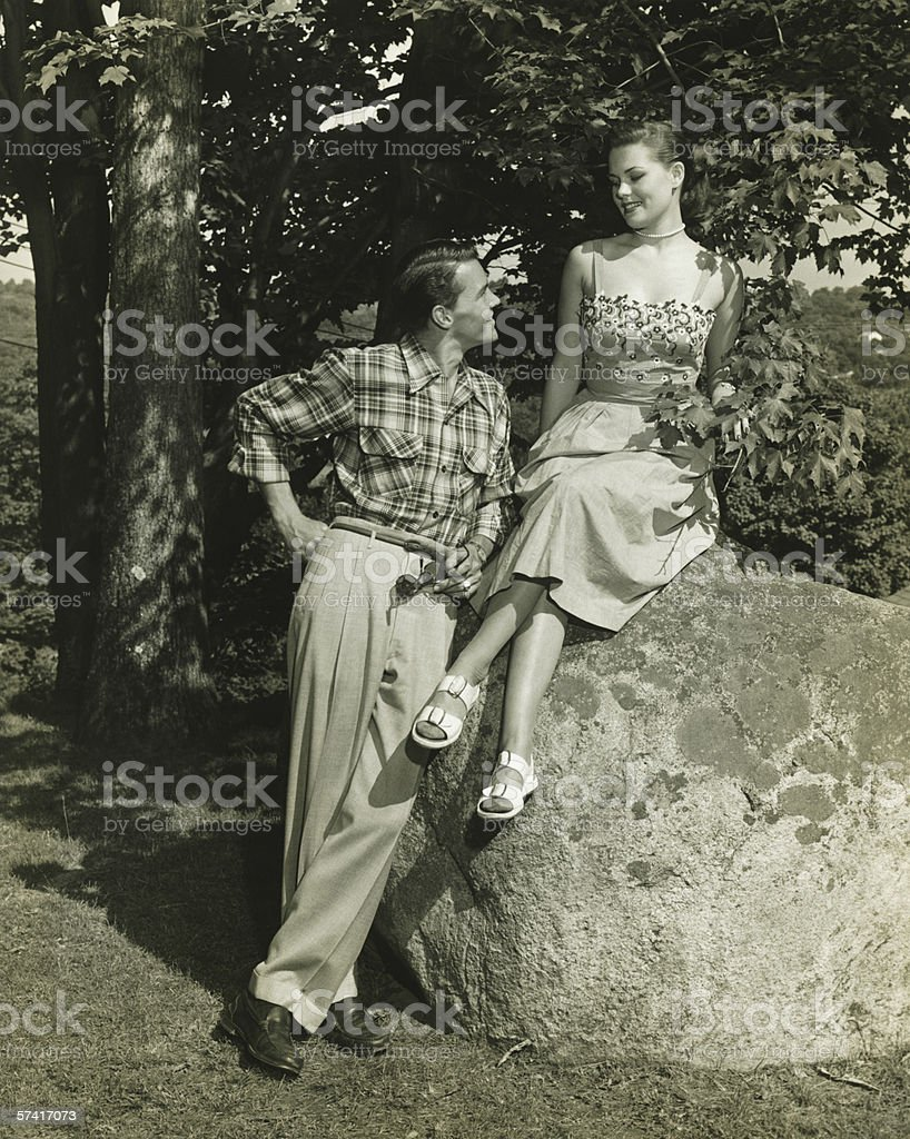 Young couple posing in park, (B&W) stock photo