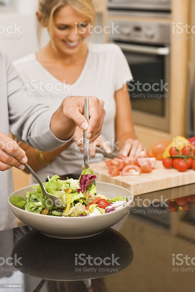 Young couple preparing vegetable salad stock photo