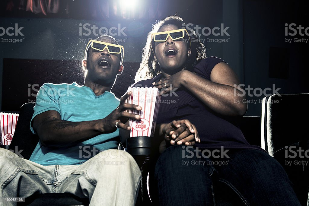 Young couple reacting in fear to a movie stock photo