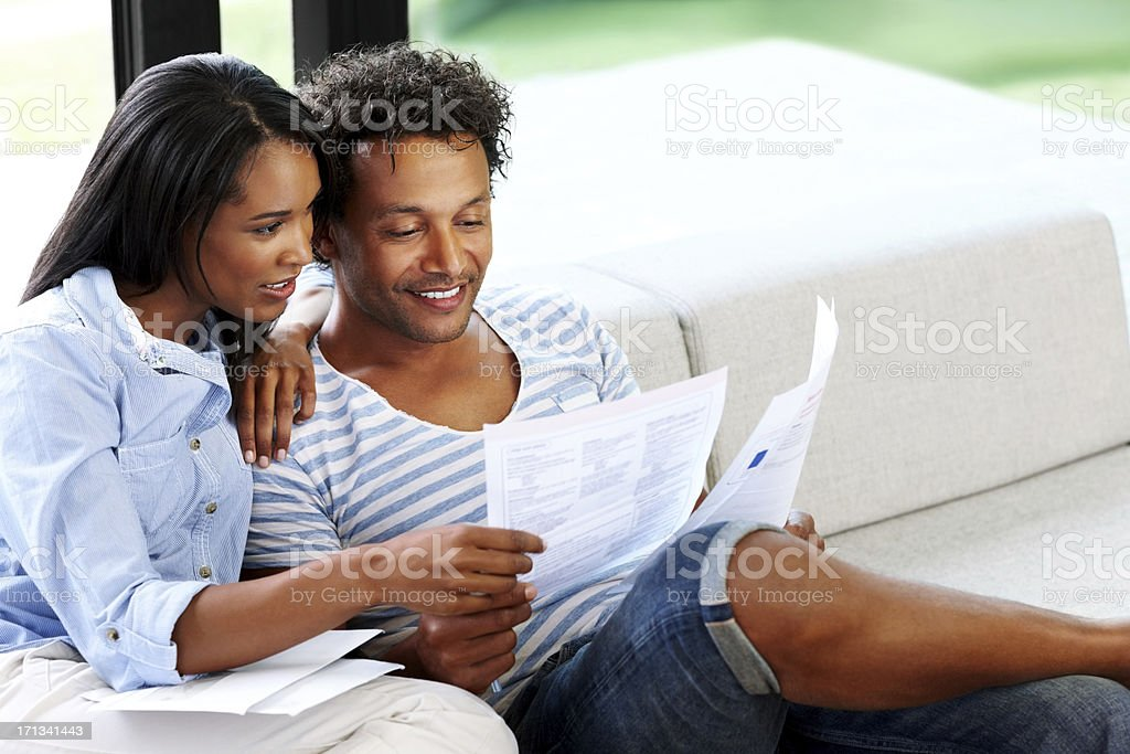 Young couple reading financial bill at home stock photo