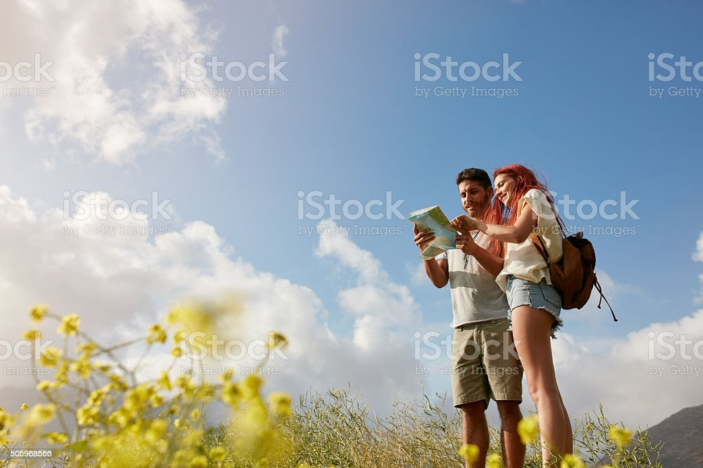 Young couple reading map on country walk stock photo
