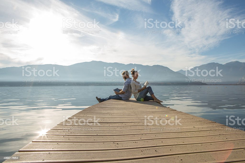 Young couple relax on lake pier with book,digital tablet stock photo