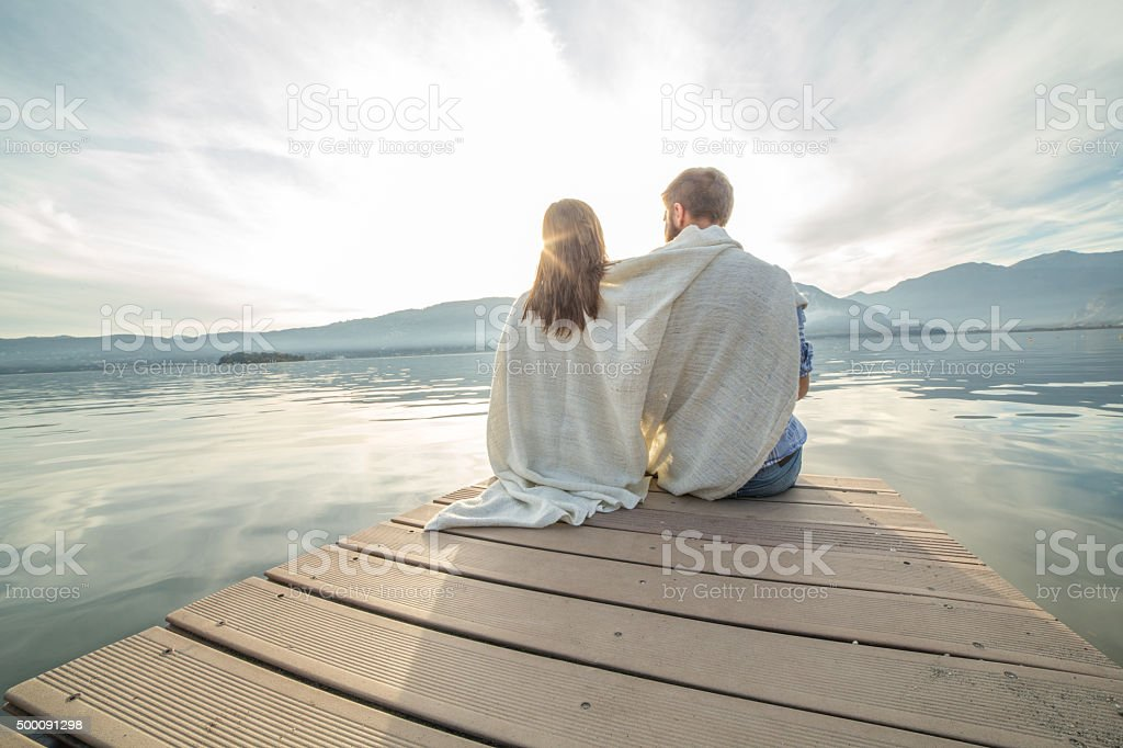 Young couple relaxes on lake pier, wrapped in blanket stock photo