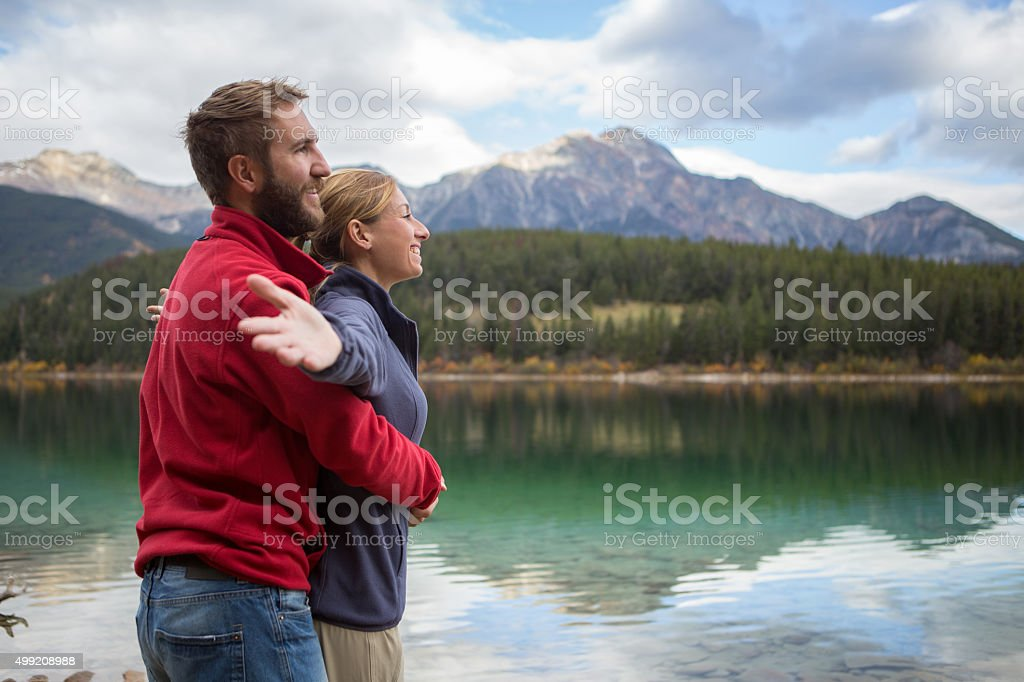 Young couple relaxing by the lake stock photo