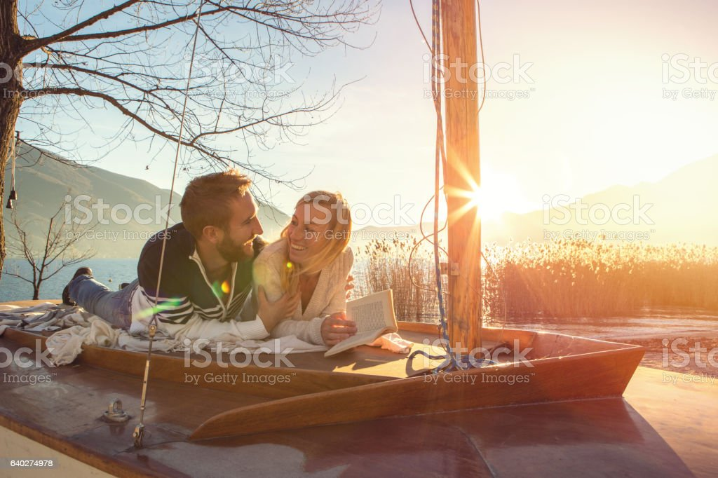 Young couple relaxing by the lake reading book stock photo