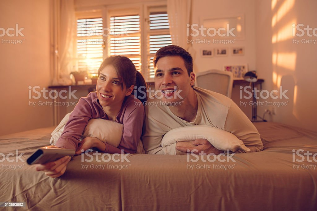 Young couple relaxing in bed watching TV. stock photo