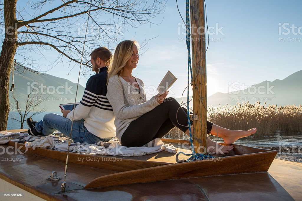 Young couple sits on a sailboat above the lake, uses a book and a...