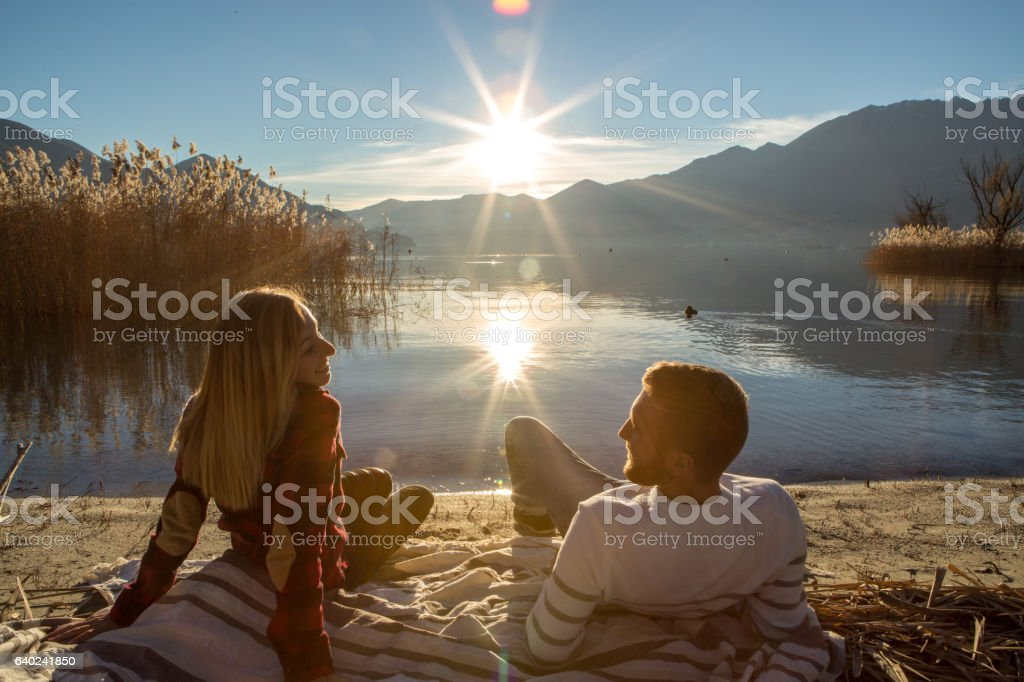 Young couple relaxing on lake beach stock photo