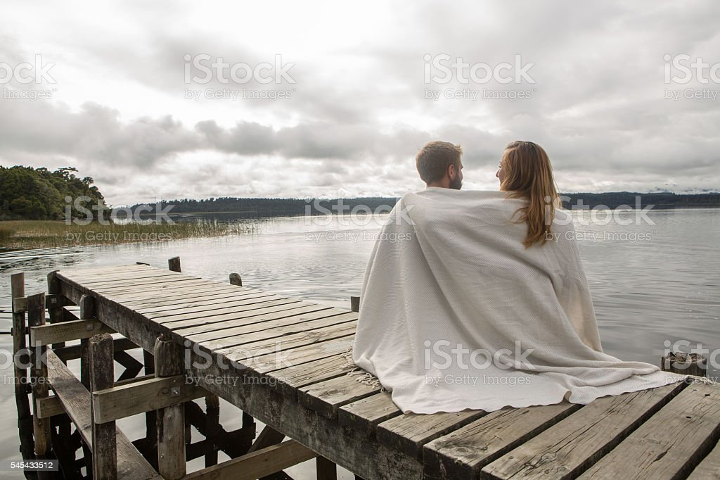 Young couple relaxing on lake pier stock photo