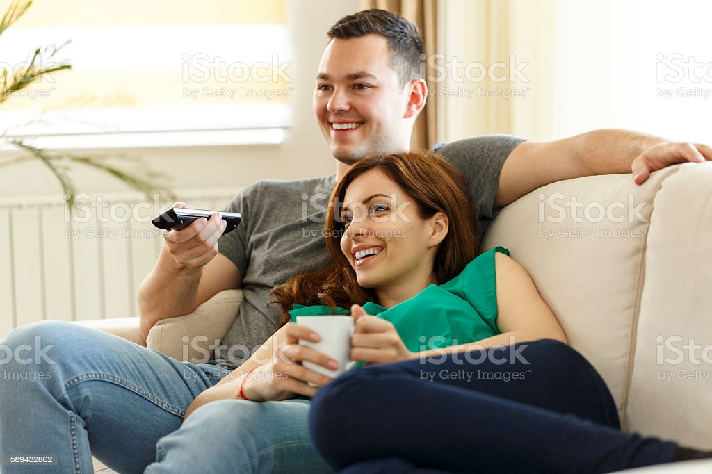 Young couple relaxing on sofa and watching television together stock photo
