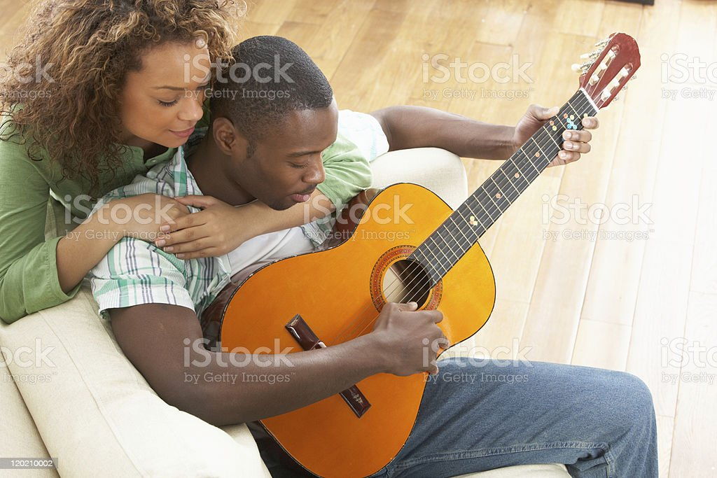 Young Couple Relaxing On Sofa Playing Acoustic Guitar royalty-free stock photo