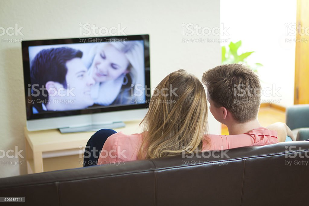 Young Couple Relaxing Watching TV Movie Together at Home stock photo
