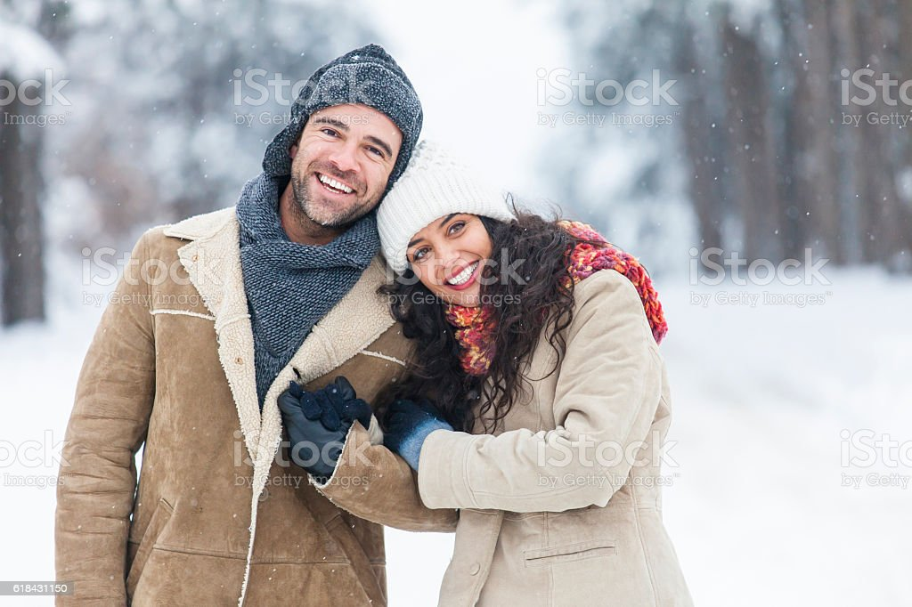Young couple resting and embracing in snow forest stock photo