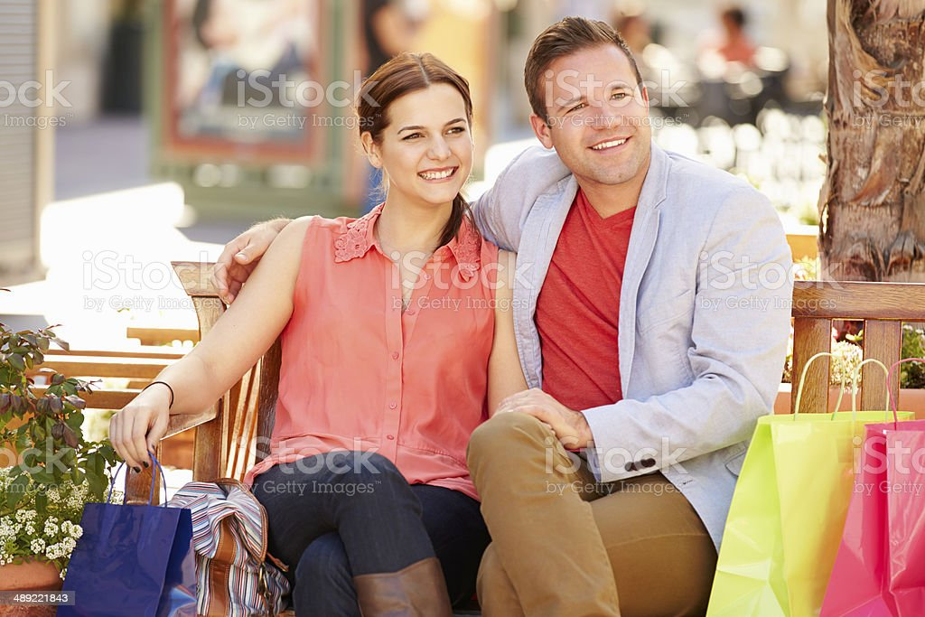 Young Couple Resting With Shopping Bags Sitting In Mall royalty-free stock photo