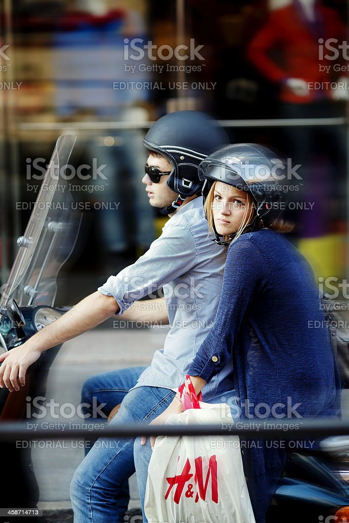 Young couple riding a scooter after shopping in Italy stock photo