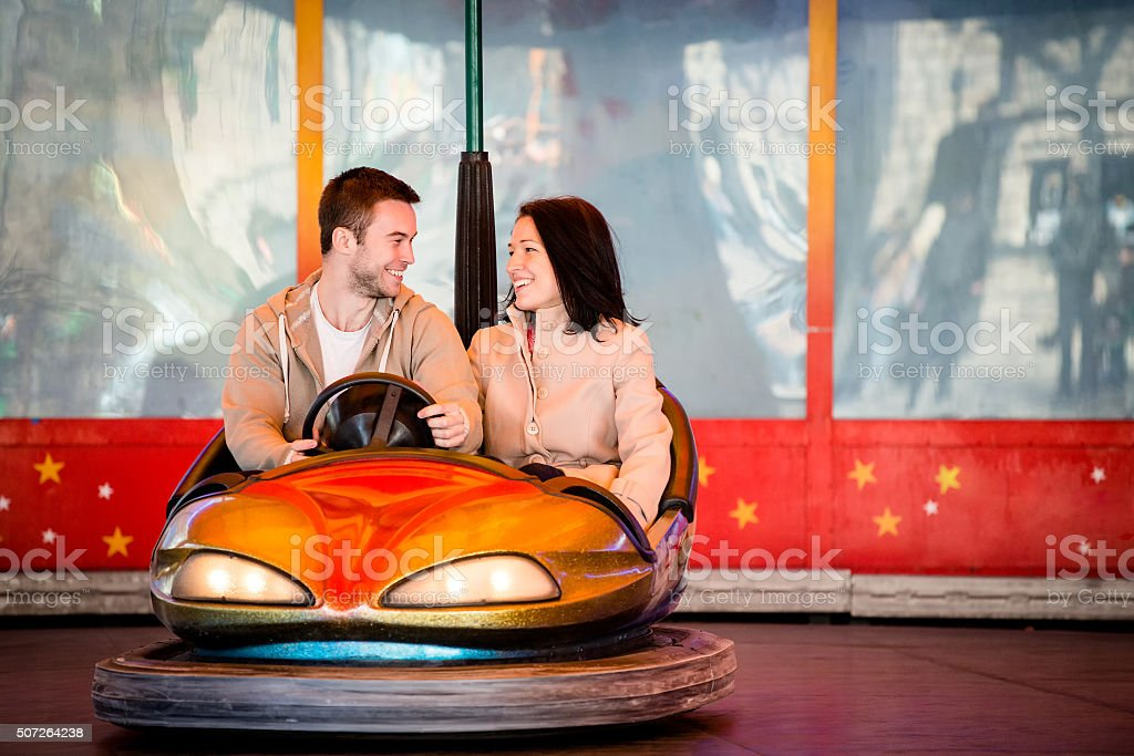 Young couple riding car in amusement park stock photo