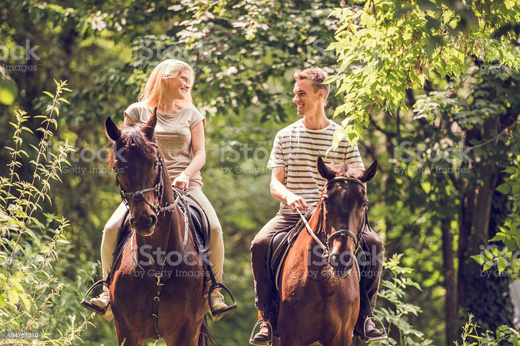 Young couple riding horses in nature and communicating. stock photo