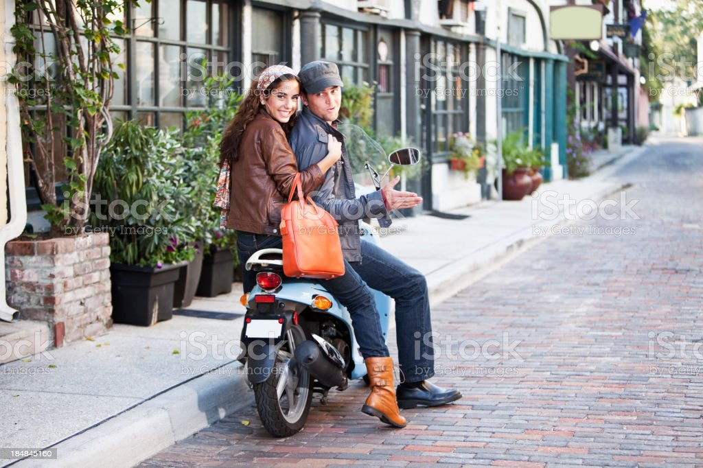 Young couple riding motor scooter on cobblestone street royalty-free stock photo