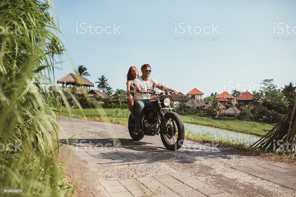 Young couple riding motorcycle on rural road stock photo