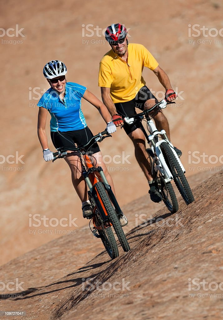 Young Couple Riding Mountain Bikes On Slickrock Trail, Utah royalty-free stock photo