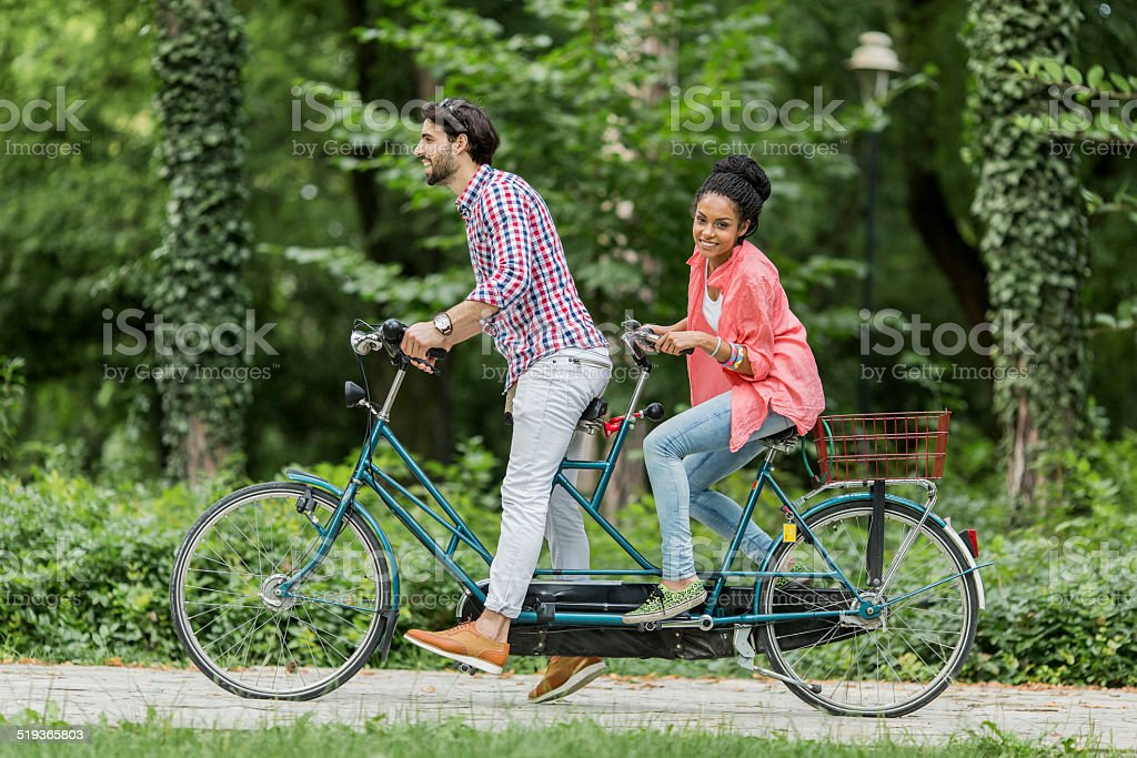 Young couple riding on the tandem bicycle stock photo