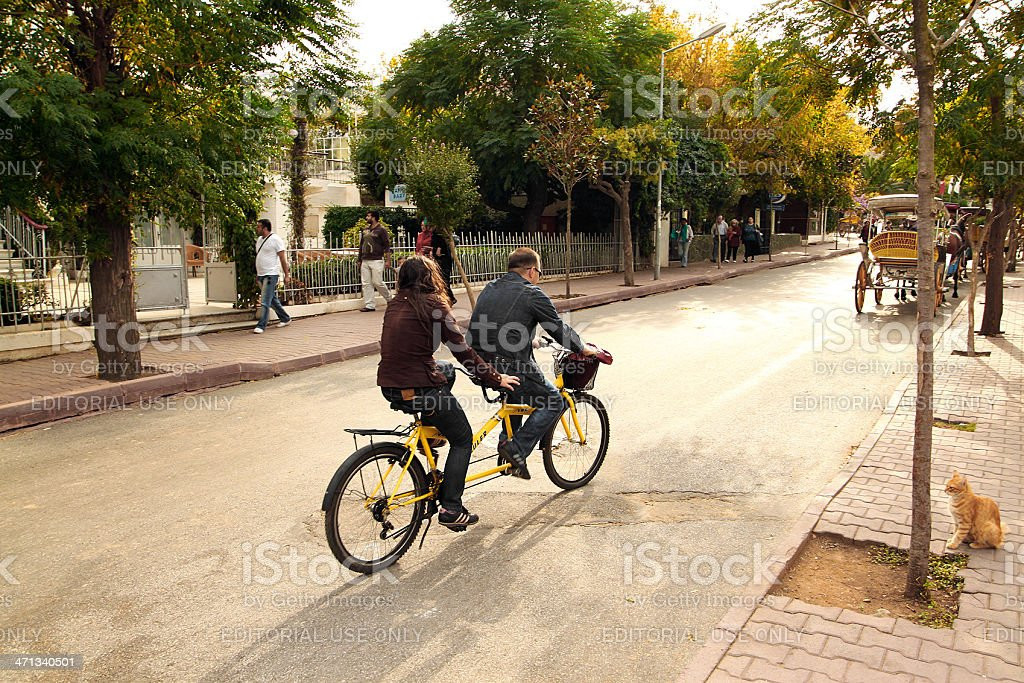 young couple riding tandem bicycle stock photo