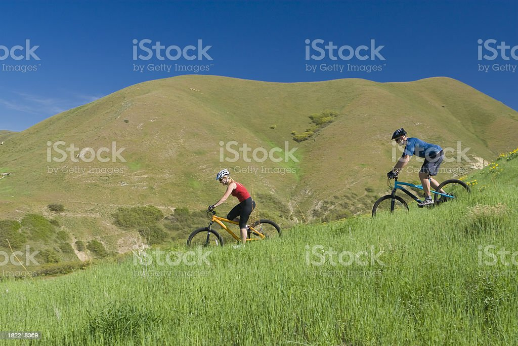 Young couple ridning mountain bikes through meadow in spring royalty-free stock photo