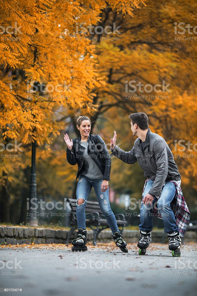 Young couple roller skating and giving high-five to each other. stock photo