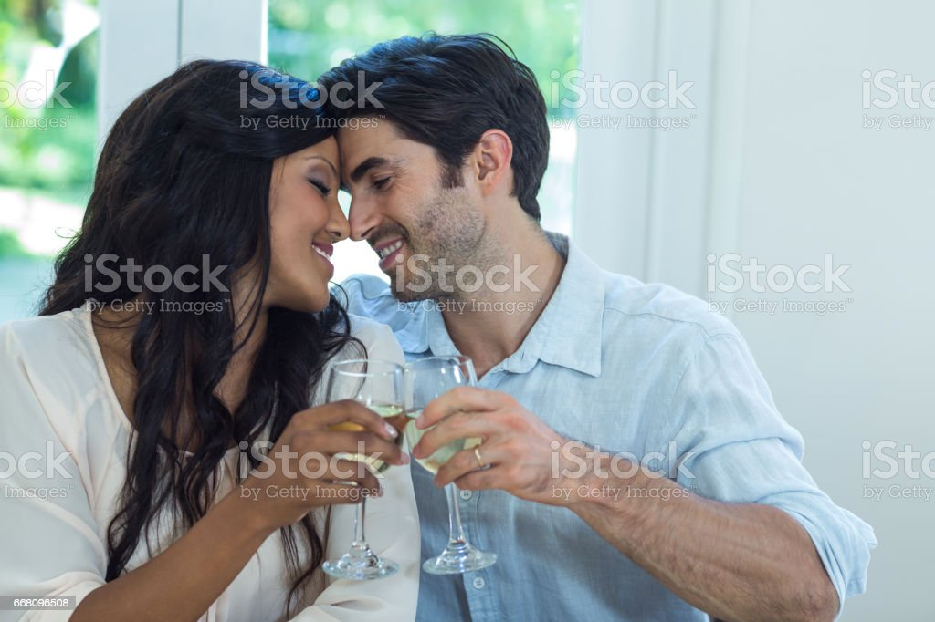 Young couple rubbing their nose while toasting wine stock photo