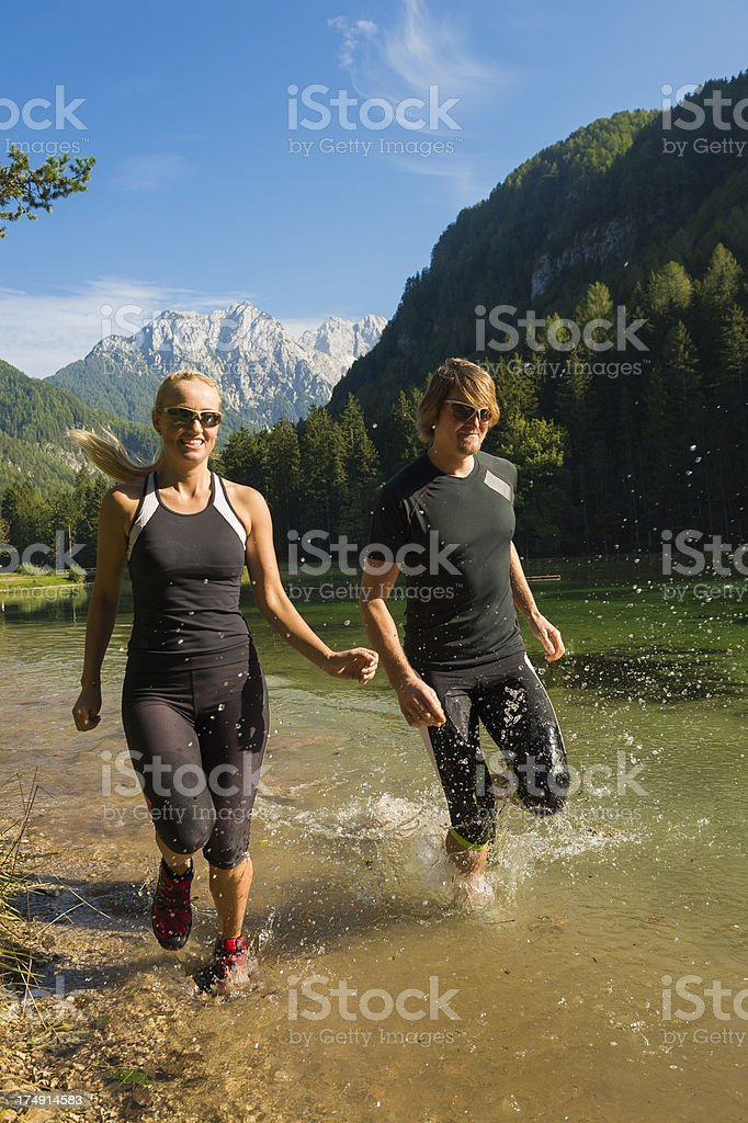 Young couple running by the lake royalty-free stock photo