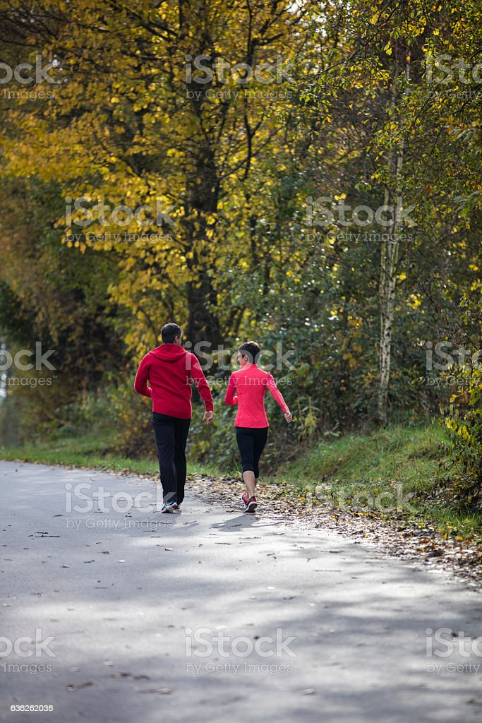 Young couple running down a road stock photo