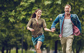 Young couple running in the park and laughing.