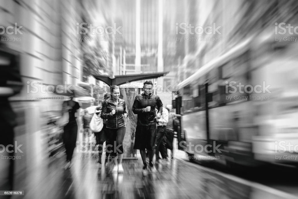 Young couple running in the rain at morning through the city streets. stock photo