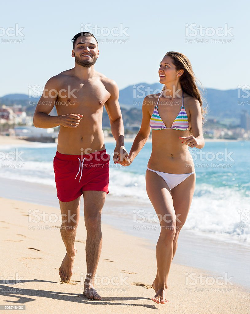 Young couple running near the sea stock photo