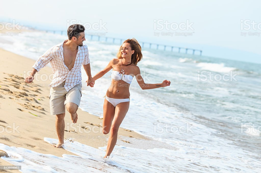 Young couple running on beach stock photo