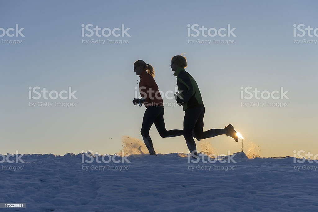 Young couple running on snow against the sunset stock photo