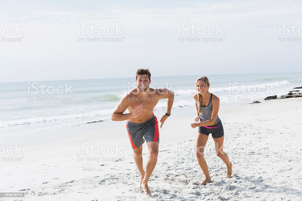 Young couple running on the beach, being playful stock photo