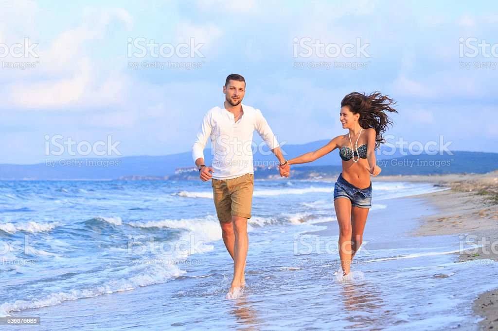 Young couple running on the beach stock photo