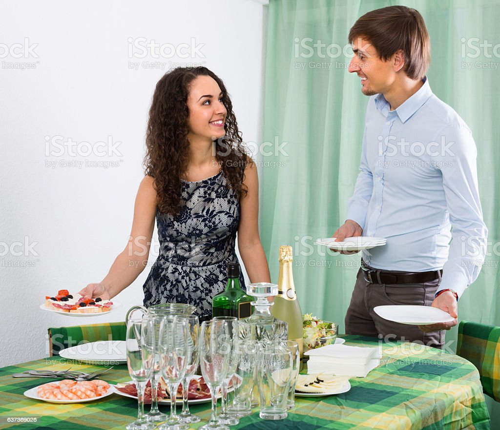 Young couple serving table at home stock photo