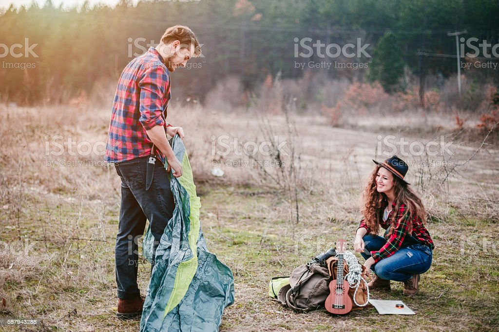 Young couple sets a tent in a campsite stock photo